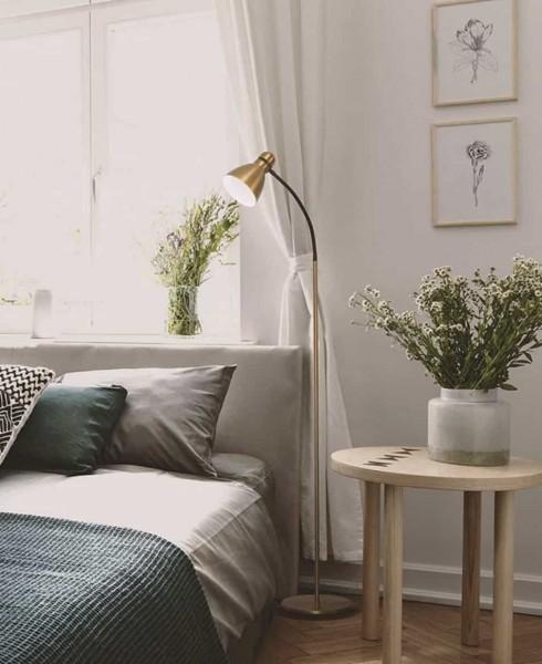 floor lamp beside a bed